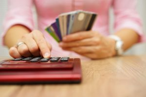 47721182 - woman calculate how much cost or spending have with credit cards